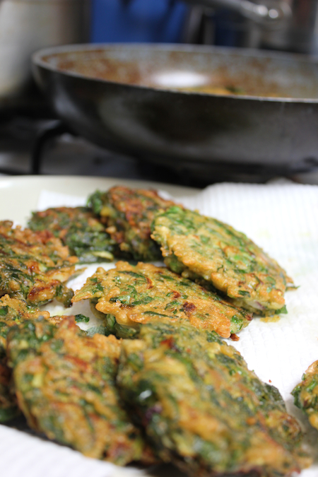 Vegan spinach zucchini and pea fritters draining