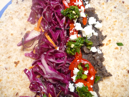 refired black beans with red cabbage slaw and zhoug on tortilla