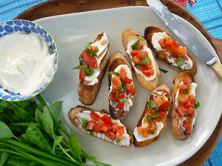 Whipped feta on bruschetta with tomato and herbs
